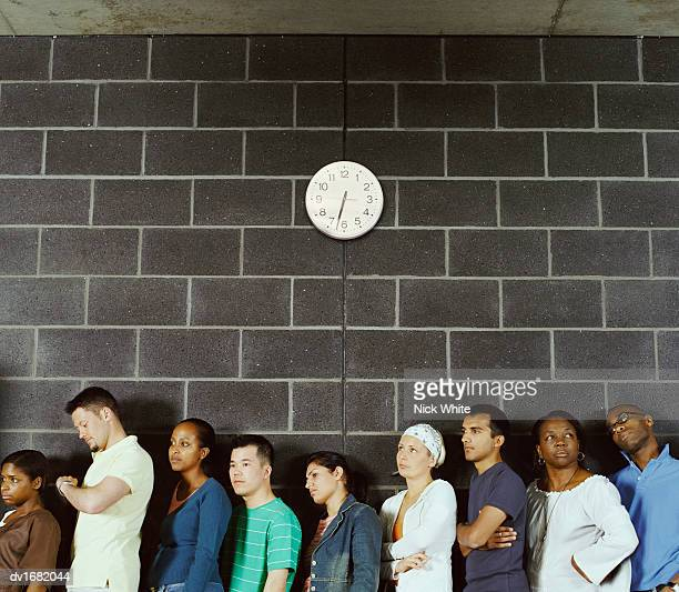 Group of Students Queuing Against a Brick Wall
