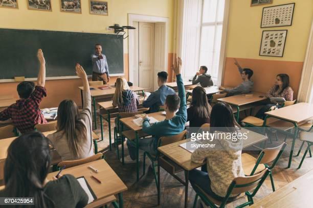 Grupo de estudiantes levantando las manos para responder a la pregunta del profesor en el aula.