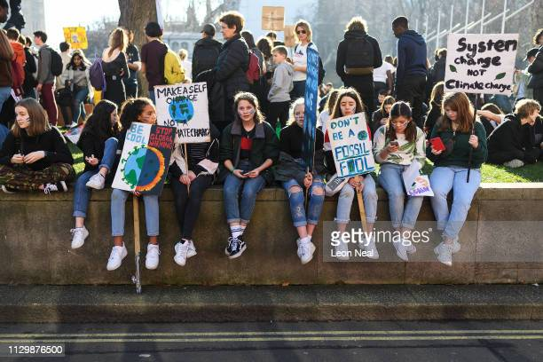 A group of students rest in Parliament Square during a climate protest on February 15 2019 in London United Kingdom Thousands of UK pupils from...