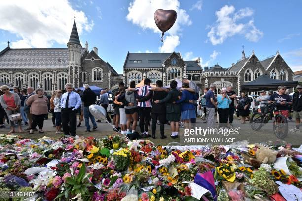 TOPSHOT A group of students sings in front of flowers left in tribute to victims at the Botanical Garden in Christchurch on March 19 four days after...