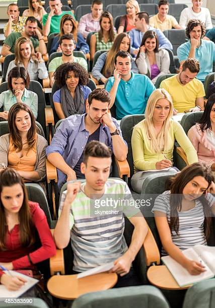 group of students sitting in amphitheatre listening to a lecture. - amphitheatre stock photos and pictures