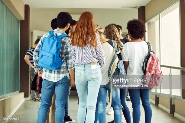 group of students standing in school corridor, rear view - highschool stock photos and pictures