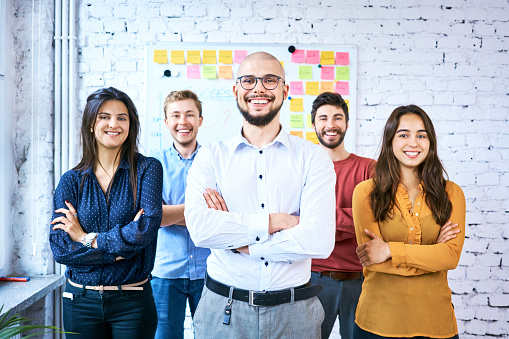 Group of students standing together in classroom and smiling. Portrait of startup entrepreneurs with arms crossed 1007730000