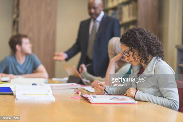 group of students study diligently in university library while a professor helps them understand the difficult concepts - american influence stock photos and pictures