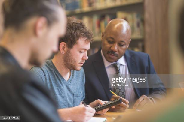 Group of students study diligently in university library while a professor helps them understand the difficult concepts