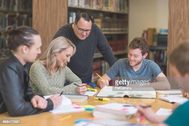 group of students study diligently in university library while a professor helps them understand the difficult concepts - master's degree stock pictures, royalty-free photos & images