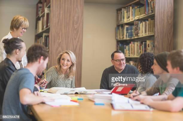 gruppe von studenten studieren fleißig in der universitätsbibliothek während professor hilft ihnen die schwierige konzepte zu verstehen - einzelveranstaltung stock-fotos und bilder