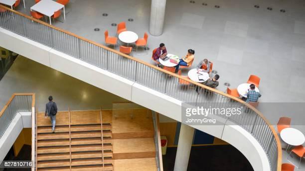 groupe d'étudiants qui étudient en mezzanine ouverte avec jeune homme sur escalier - mezzanine photos et images de collection