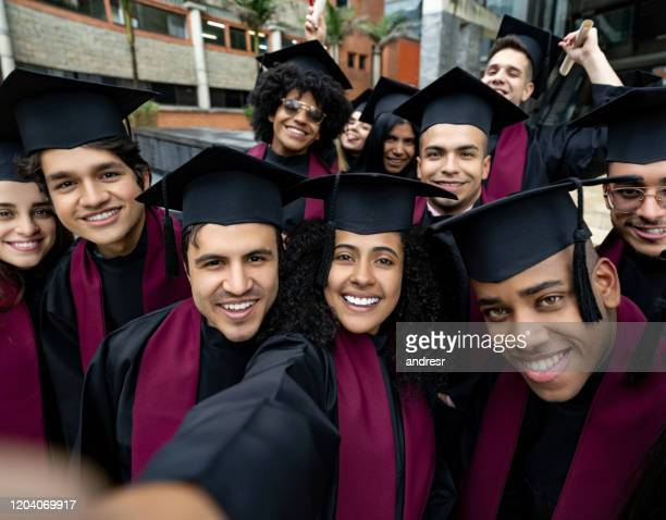 group of students taking a selfie on graduation day - alumni stock pictures, royalty-free photos & images