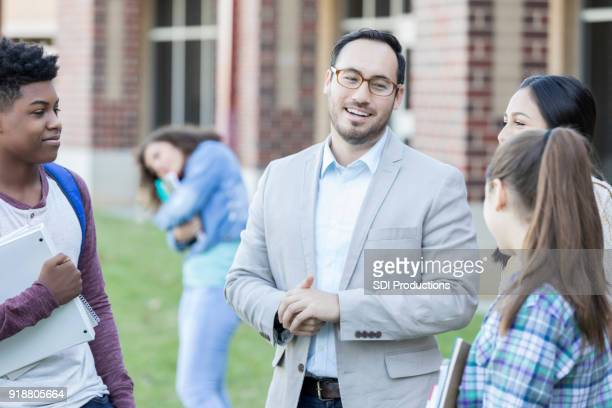 Group of students talk with principal before school