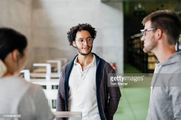 group of students talking in public library together - north african ethnicity stock pictures, royalty-free photos & images