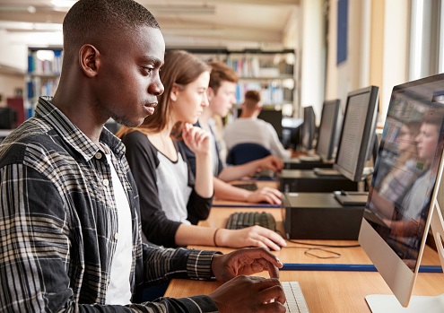 Group Of Students Using Computers In College Library 879041304