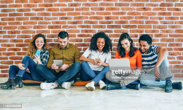 group of students using mobile devices - multimedia stock pictures, royalty-free photos & images