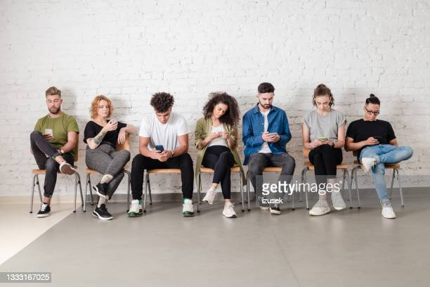 group of students using mobile phones - izusek stock pictures, royalty-free photos & images
