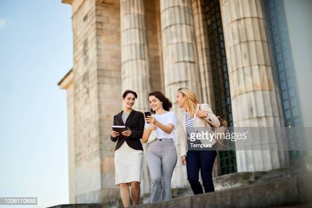 group of students walking outside the university. - universidad stock pictures, royalty-free photos & images