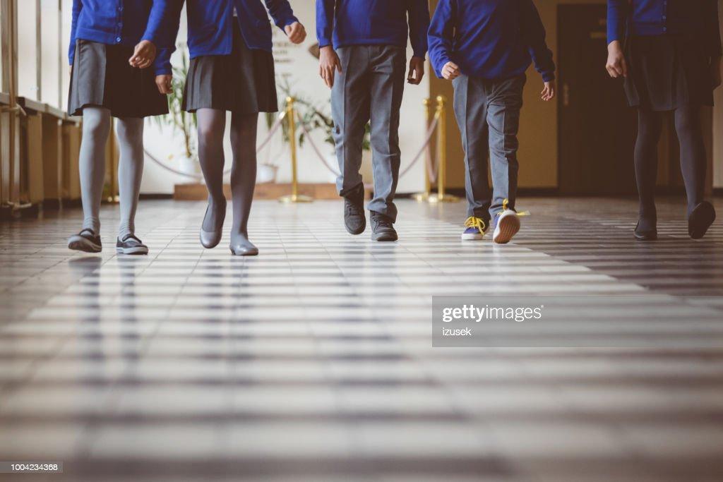Group of students walking through school hallway : Stock Photo