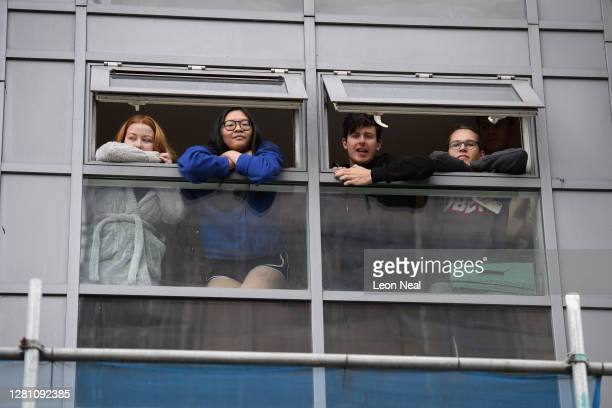 Group of students who have tested positive for COVID-19 are interviewed from their apartment window, after being informed that they must leave the...