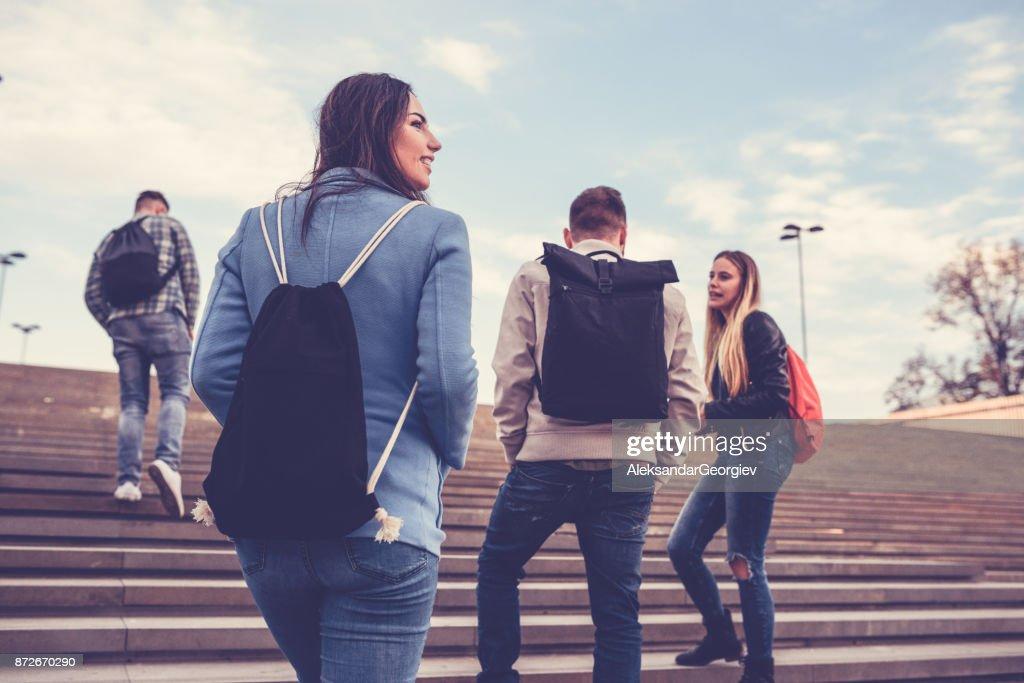 Grupo de estudiantes con mochilas caminando a la escuela : Foto de stock
