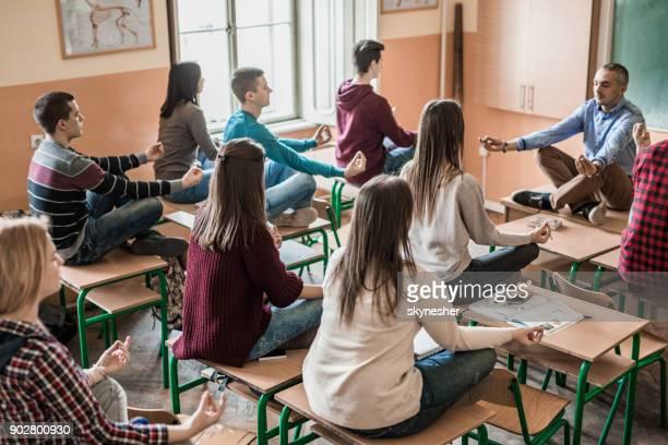 Grupo de estudiantes con su profesor de meditación en el aula.