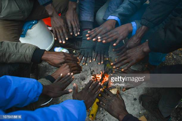 Group of Sudanese migrants seen near Ouistreham ferry terminal warming their hands over a fire. Since the beginning of December, there has been a...
