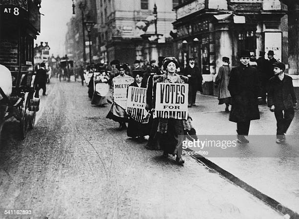 A group of suffragettes marching for women's voting rights circa 1910 They are wearing placards reading 'Votes For Women' One demonstrator is wearing...