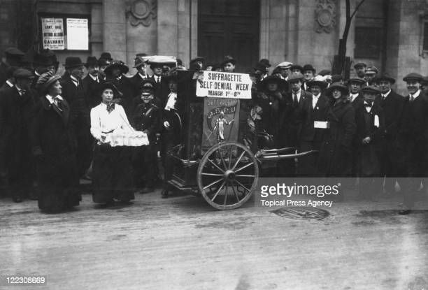 Group of suffragettes with a piano organ on Kingsway, London, 3rd March 1913. The sign on the organ reads 'Suffragette Self-Denial Week, March...