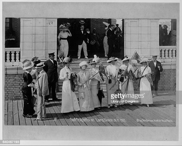 A group of suffragists wave banners reading Votes of Women on the porch front of a building at Long Beach New York USA