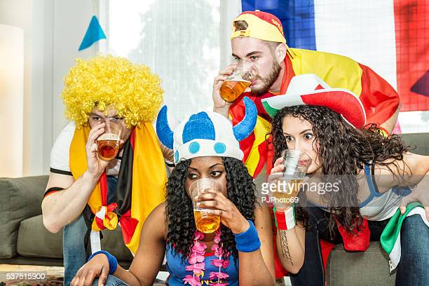 Group of supporters drinking beer at home