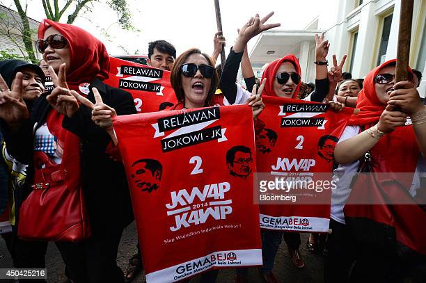 A group of supporters holding red banners and showing pictures of Joko Widodo governor of Jakarta and presidential candidate and Jusuf Kalla vice...
