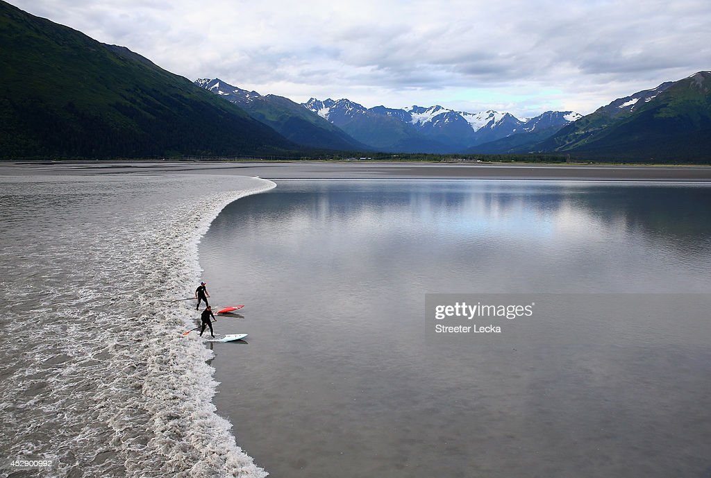 A group of surfers catch the Bore Tide near a small town called Girdwood at Turnagain Arm on July 15, 2014 in Anchorage, Alaska. Alaska's most famous Bore Tide, occurs in a spot on the outside of Anchorage in the lower arm of the Cook Inlet, Turnagain Arm, where wave heights can reach 6-10 feet tall, move at 10-15 mph and the water temperature stays around 40 degrees Fahrenheit. This years Supermoon substantially increased the size of the normal wave and made it a destination for surfers.