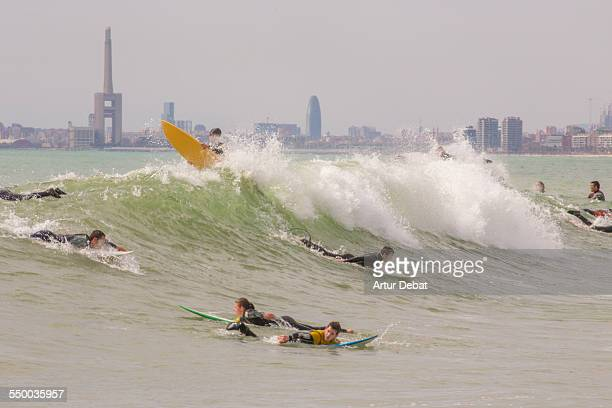 Group of surfers on the wave with Barcelona city