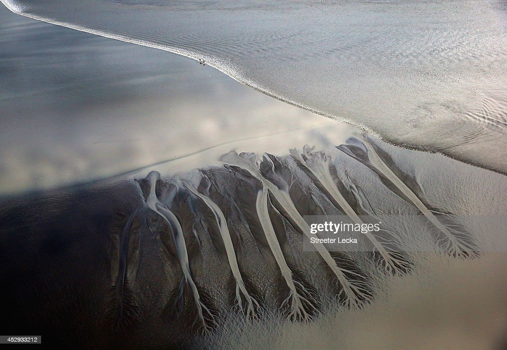 A group of surfers ride the Bore Tide at Turnagain Arm on July 15, 2014 in Anchorage, Alaska. Alaska's most famous Bore Tide, occurs in a spot on the outside of Anchorage in the lower arm of the Cook Inlet, Turnagain Arm, where wave heights can reach 6-10 feet tall, move at 10-15 mph and the water temperature stays around 40 degrees Fahrenheit. This years Supermoon substantially increased the size of the normal wave and made it a destination for surfers.