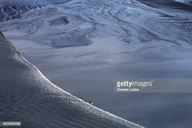 A group of surfers ride the Bore Tide at Turnagain Arm on July 15 2014 in Anchorage Alaska Alaska's most famous Bore Tide occurs in a spot on the...