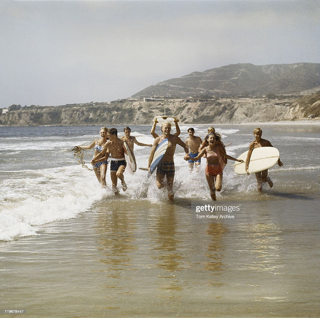 Group of surfers running in water with surfboards, smiling : Stock Photo