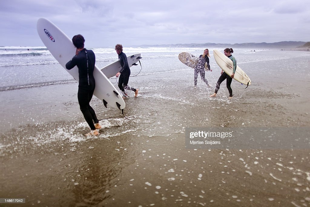 Group of surfers splashing each other while walking along shoreline. : Stockfoto