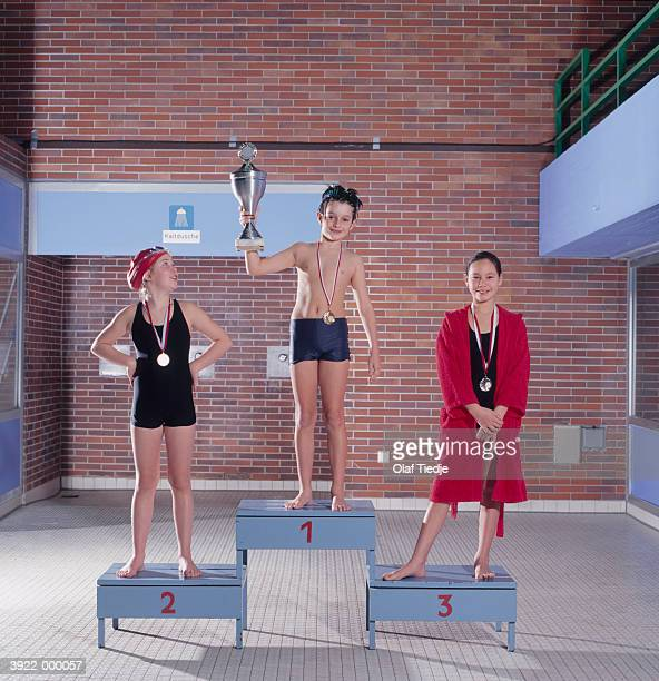 group of swimmers on podium - winners podium stock pictures, royalty-free photos & images