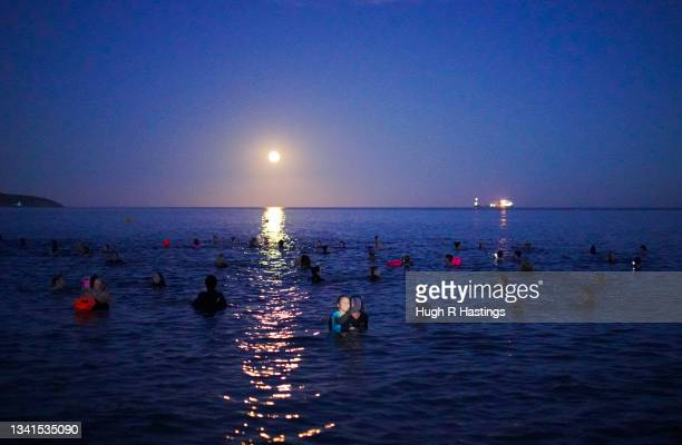 Group of swimmers take a selfie as they swim under the Harvest Moon on September 20, 2021 in Swanpool Beach, Falmouth, England.