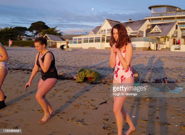 Group of swimmers take to the sea at the first sunrise of the year at Gyllyngvase Beach on January 1, 2021 in Falmouth, United Kingdom. January 1st...