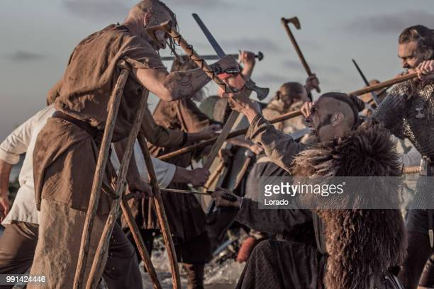 A group of sword wielding bloody medieval viking warriors clashing on a cold seashore