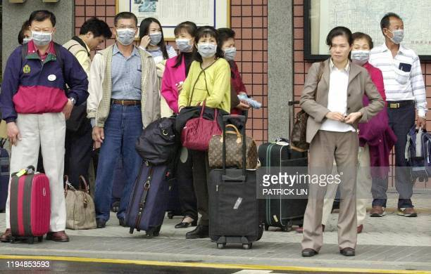 Group of Taiwan tourists wear protective masks while waiting outside the lobby of Taipei airport, 07 April 2003. The scare of the fatal Severe Acute...