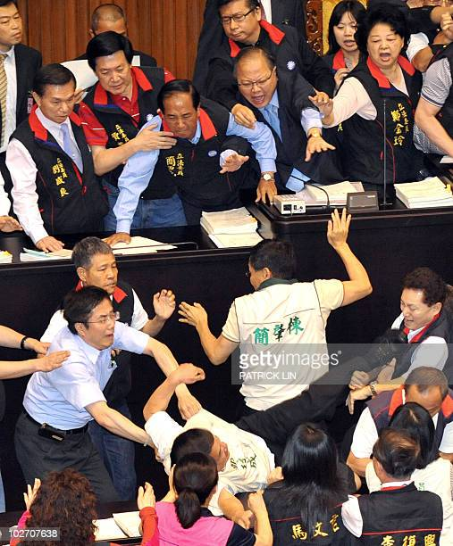 A group of Taiwanese opposition legislators are stopped by their counterparts from the ruling party as they try to edge their way to the podium of...