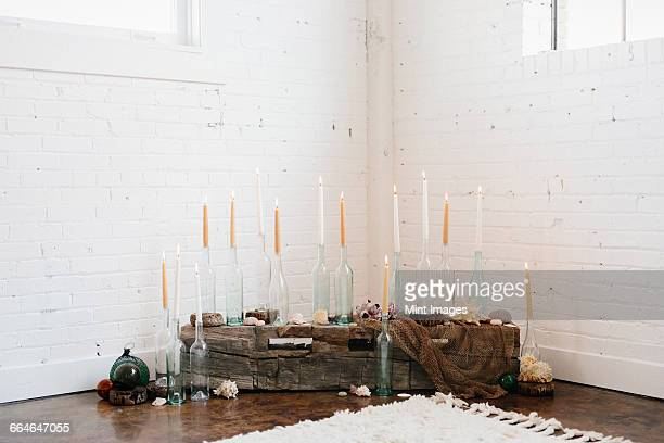 A group of tall lit candles in clear glass bottles arranged in a corner.