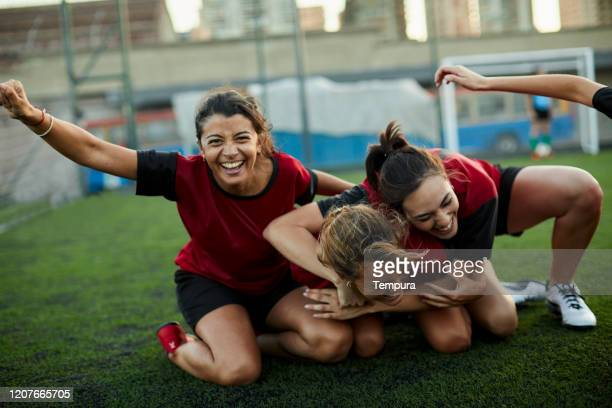 group of team mates celebrate a goal embracing in the ground. - soccer competition stock pictures, royalty-free photos & images