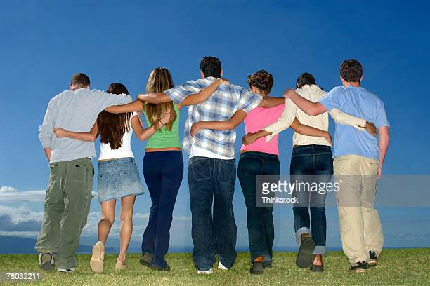 group of teen boys and girls walking away from the viewer with arms around each other - arm in arm stock pictures, royalty-free photos & images