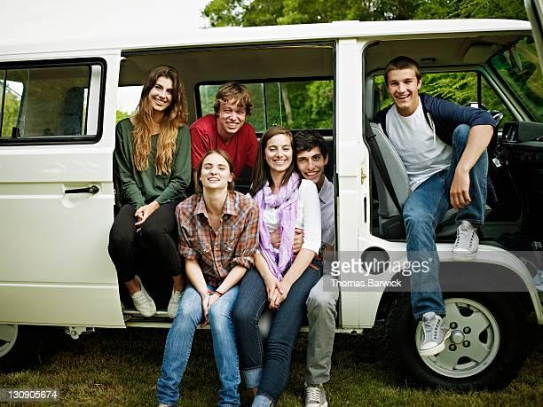 Group of teen friends sitting in side door of van