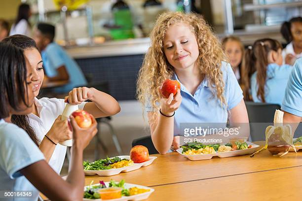 Group of teen girls having healthy lunch together at school