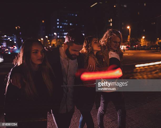 Group of teen hipster friend walking in town at night
