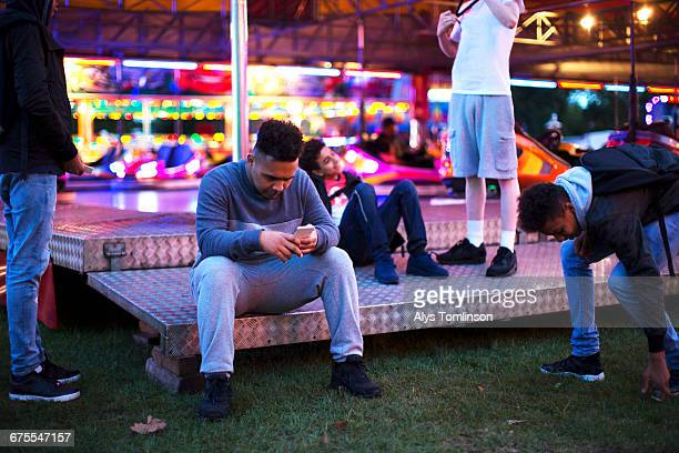 group of teenage boys at fairground - boredom stock pictures, royalty-free photos & images