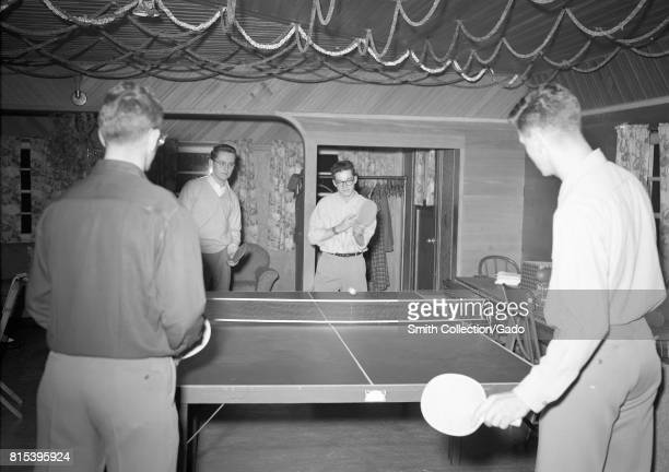 A group of teenage boys play doubles table tennis indoors with one boy having just hit the ball over the net Eureka California 1950