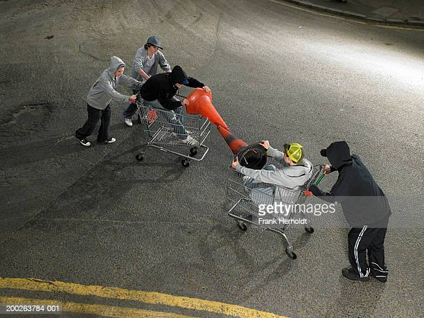Group of teenage boys (13-15) play fighting in shopping trolleys